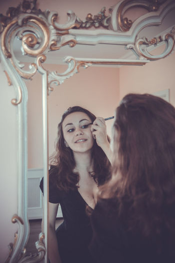 Young woman applying eyeliner while looking in mirror