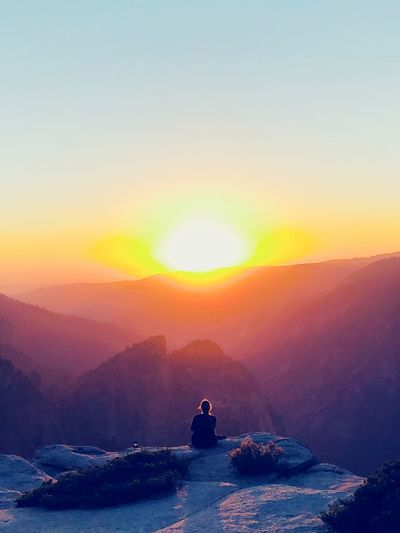 Rear view of woman sitting on cliff by mountains against sky during sunrise