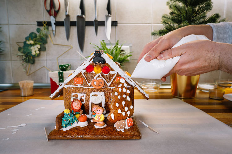 Midsection of person decorating christmas gingerbread house in kitchen at home