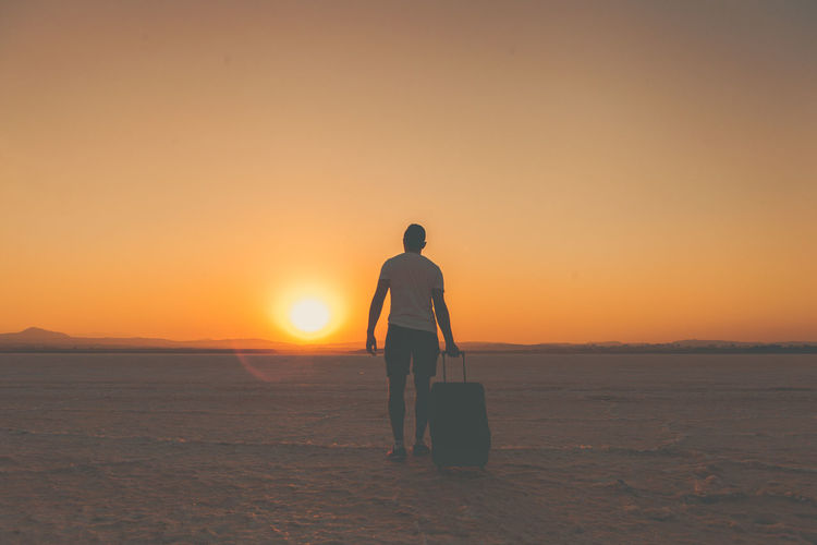 Rear View Of Man Walking With Suitcase On Snow Field Against Sky During Sunset