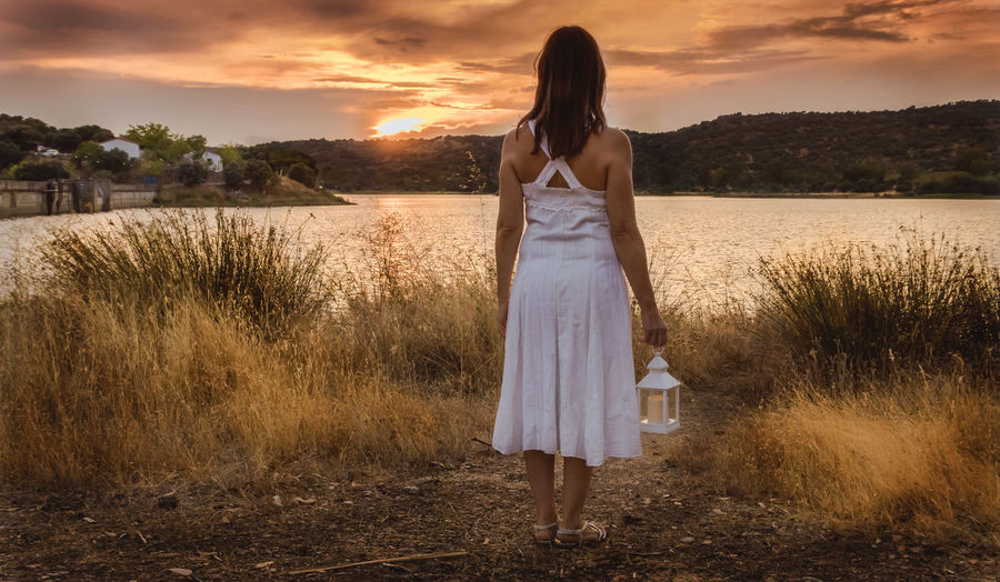 Woman watching the sunset with white dress and lantern Standing Sky Full Length Women Leisure Activity One Person Sunset Casual Clothing Land Lifestyles Nature Plant Adult Real People Fashion Dress Cloud - Sky Rear View Tranquility Hairstyle Hair Outdoors Beautiful Woman