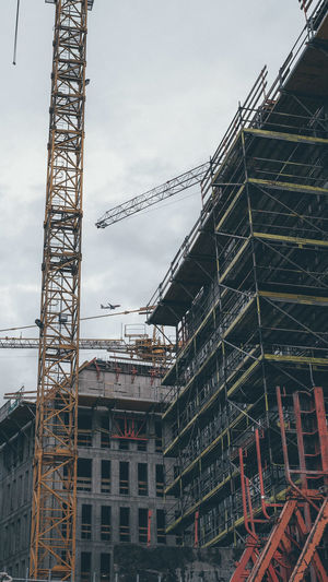 Low angle view of crane at construction site against sky in city