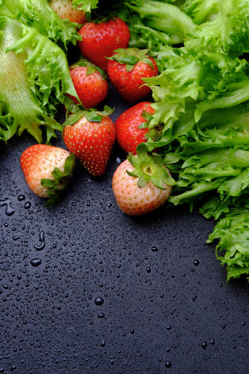 High angle view of strawberries with lettuce on wet table