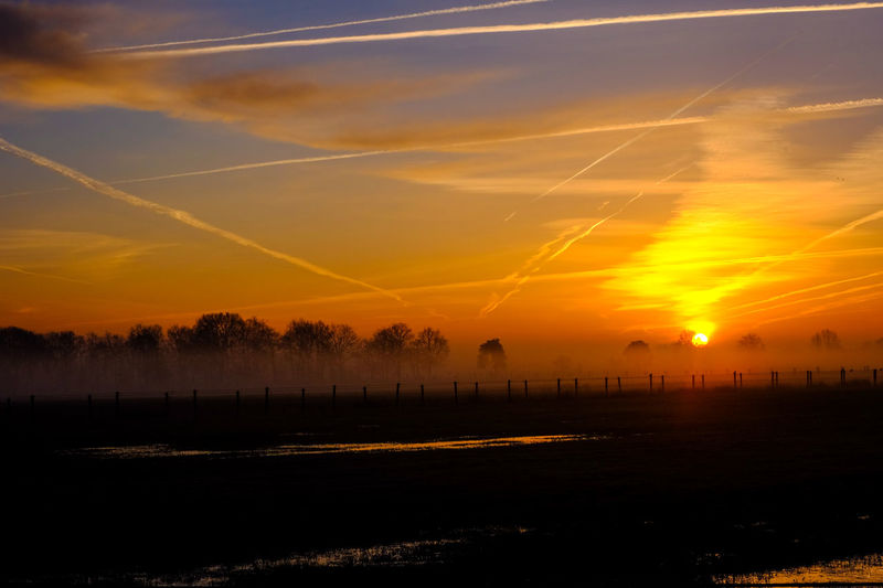 Countryside winter sunrise landscape Architecture Beauty In Nature Cloud - Sky Environment Idyllic Landscape Nature No People Orange Color Outdoors Scenics - Nature Silhouette Sky Sun Sunlight Sunset Tranquil Scene Tranquility Tree Vapor Trail Water