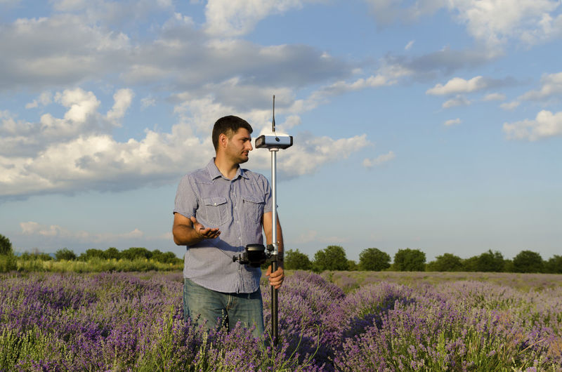 Surveyor with theodolite on lavender field against sky