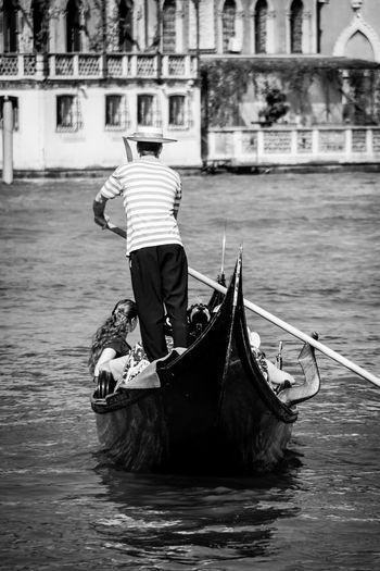 Rear view of man rowing gondola at grand canal