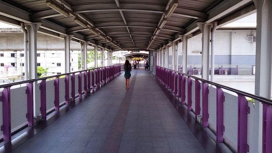 Rear View Of Woman Walking In Footbridge In City