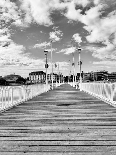 Empty pier on bridge against sky