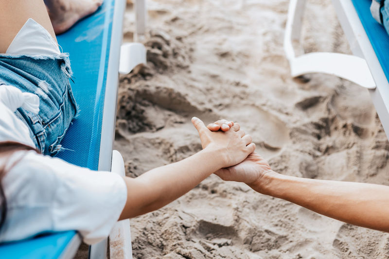 Low section of man holding hands on sand