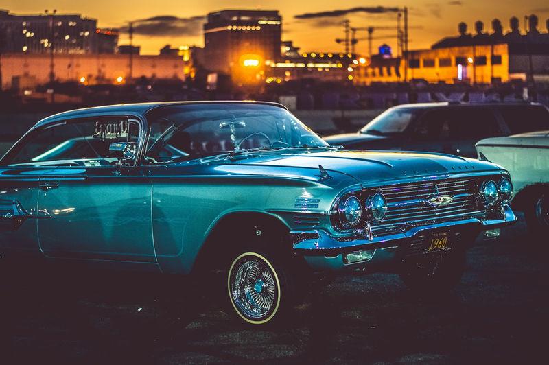 Vintage car on illuminated city during sunset