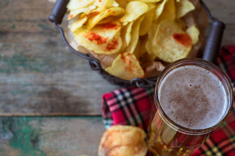 High angle view of potato chips by beer on table