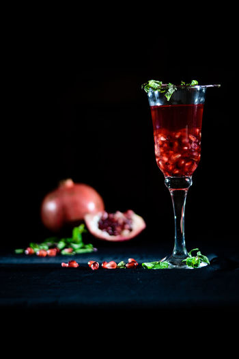 Pomegranate juice in glass on table against black background