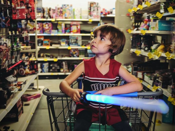 Boy sitting in shopping cart at toy shop