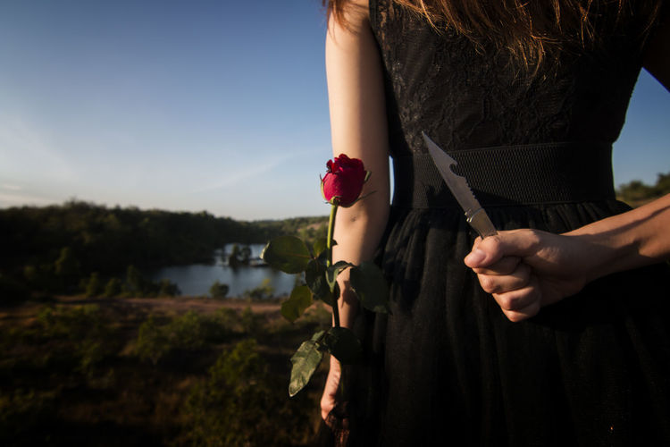 Midsection rear view of woman holding knife and rose behind her back on land