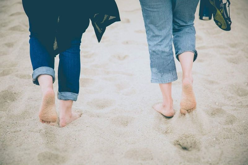 Low Section Human Leg Jeans Barefoot Beach Walking Sand Togetherness Casual Clothing Leisure Activity Day Real People Vacations Freshness Feet