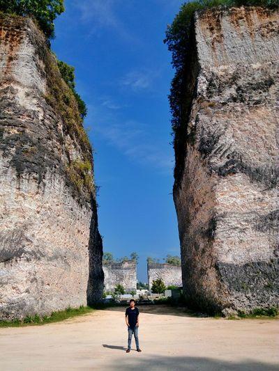 Mid distance view of man standing against rock formations at garuda wisnu kencana