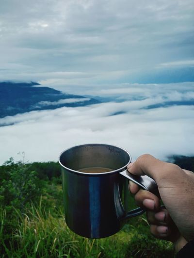 Midsection of person holding coffee cup against sky