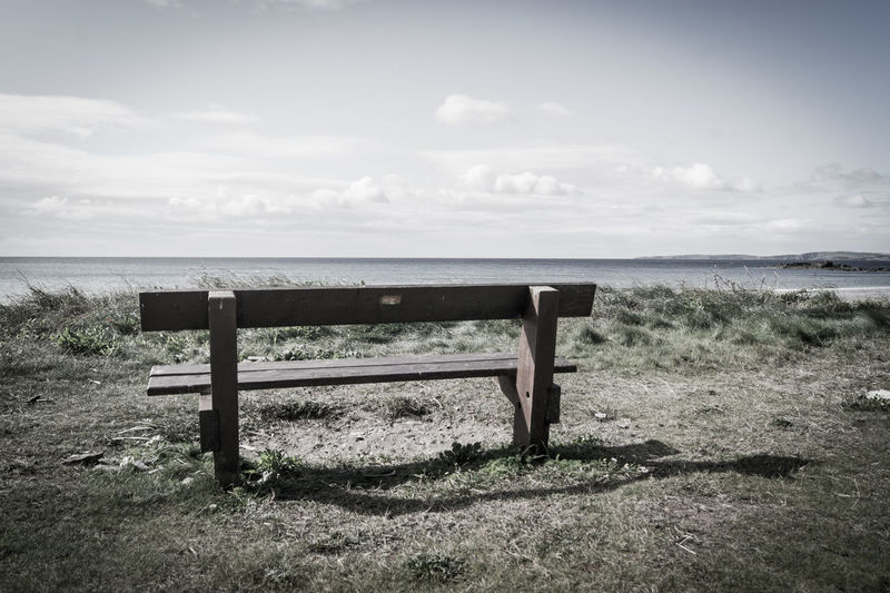 Empty bench on beach against sky