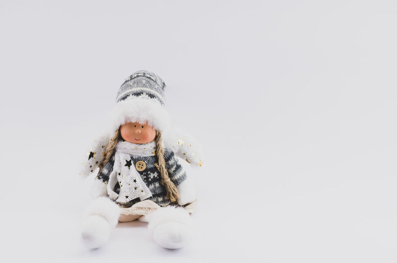 Christmas time doll Studio Shot Winter Childhood Warm Clothing One Person Child Cute Indoors  Cold Temperature Front View Clothing Snow Innocence White Background Full Length Representation Copy Space Sitting Christmas Ornament Wintertime Toy Figurine  Dolls