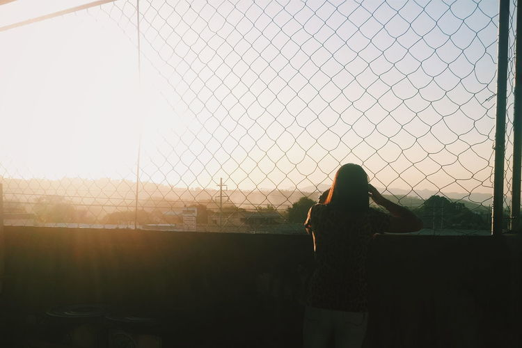 Rear view of woman standing by fence against sky
