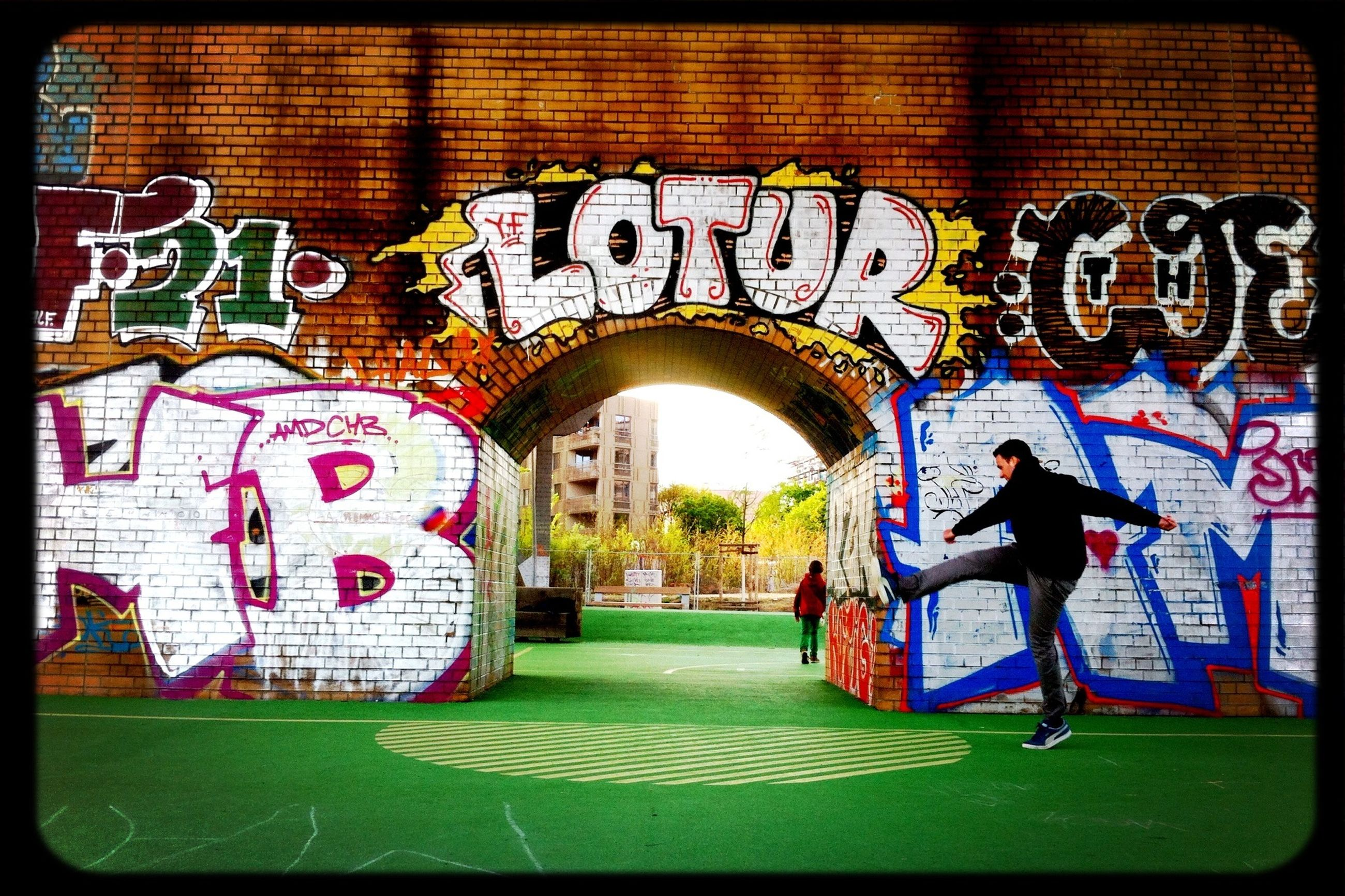 architecture, built structure, building exterior, arch, graffiti, art and craft, art, wall - building feature, entrance, creativity, full length, text, transfer print, outdoors, grass, day, auto post production filter, wall, gate