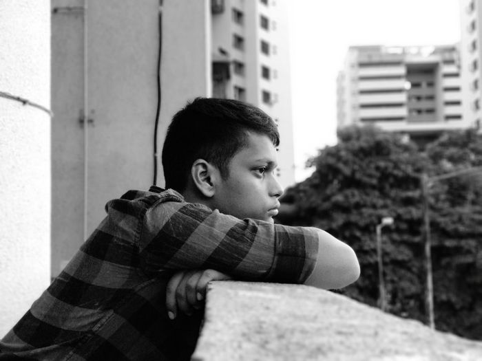 Boy leaning on railing in balcony