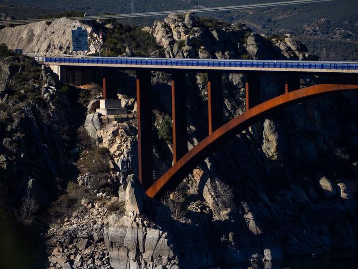 Bridge over stream amidst mountains