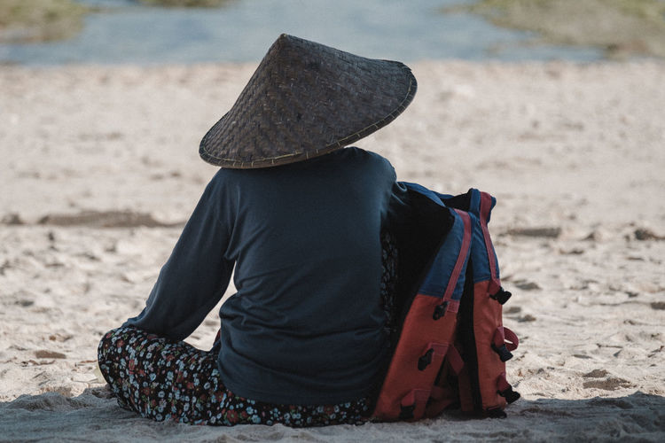 Rear View Of Woman Sitting On Sand At Beach