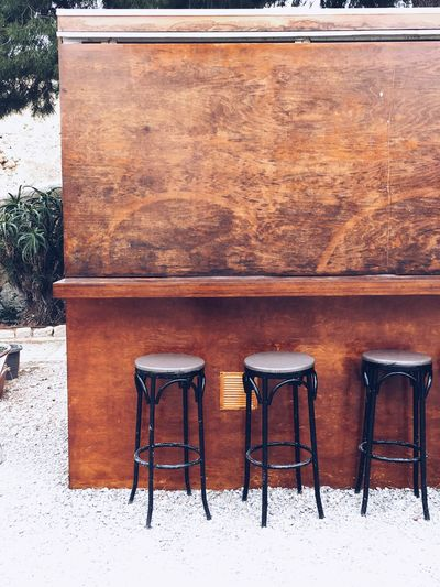 Empty chairs and table against wall during winter