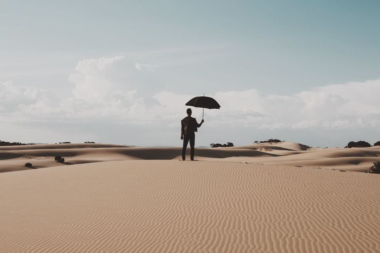 Rear View Of Man Holding Umbrella On Desert Against Sky