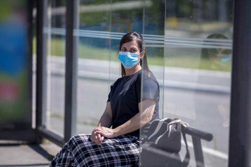 Woman with face mask sitting at bus stop