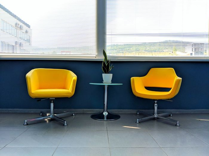 Empty seats by potted plant on table in office