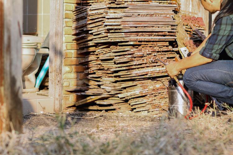 Man working on log stack of logs