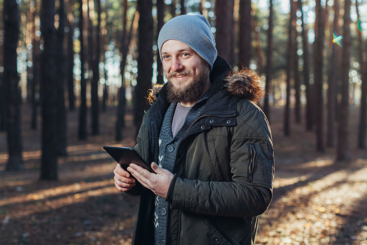 Smiling bearded young man holding digital tablet in forest