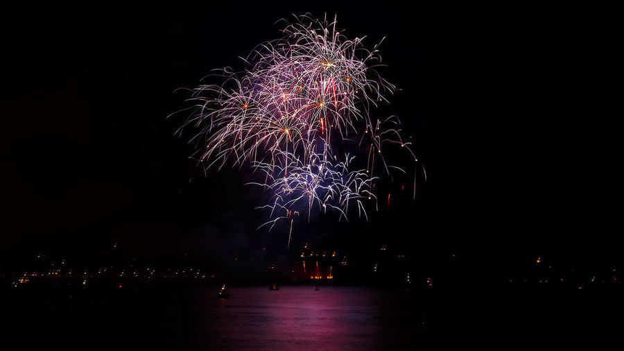 Architecture Arts Culture And Entertainment Building Exterior Built Structure Celebration City Cityscape Event Exploding Firework Firework - Man Made Object Firework Display Illuminated Light Long Exposure Motion Multi Colored Nature Night No People Outdoors Sky Water