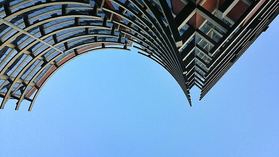 Directly Below Shot Of Modern Building Against Clear Blue Sky