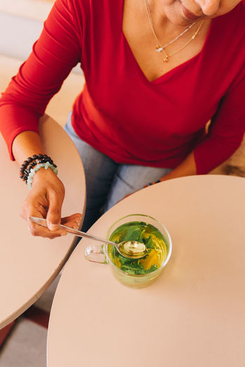 Midsection of woman holding drink sitting on table