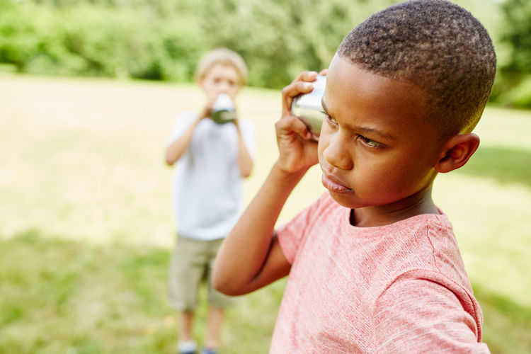 Close-up of cute kids communicating through tin can phone at park