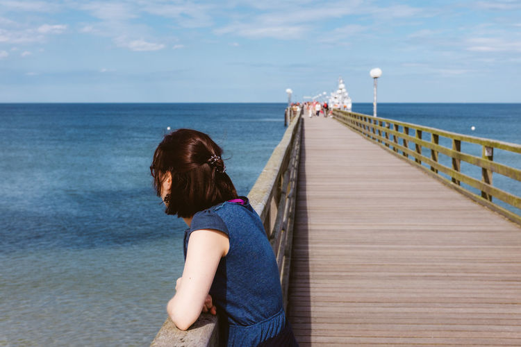 Side view of young woman standing on pier over sea
