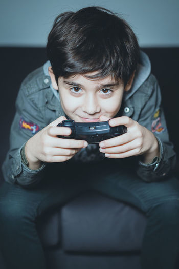 Boys One Person Child Front View Males  Holding Men Childhood Leisure Activity Indoors  Lifestyles Portrait Technology Wireless Technology Communication Casual Clothing Mobile Phone Real People Video Game  Innocence Playstation Game Playing