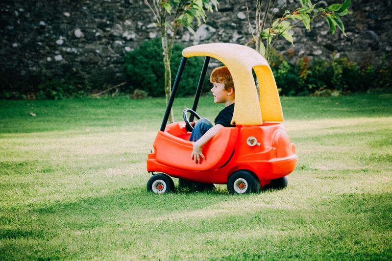 Boy sitting in toy car on grassy field