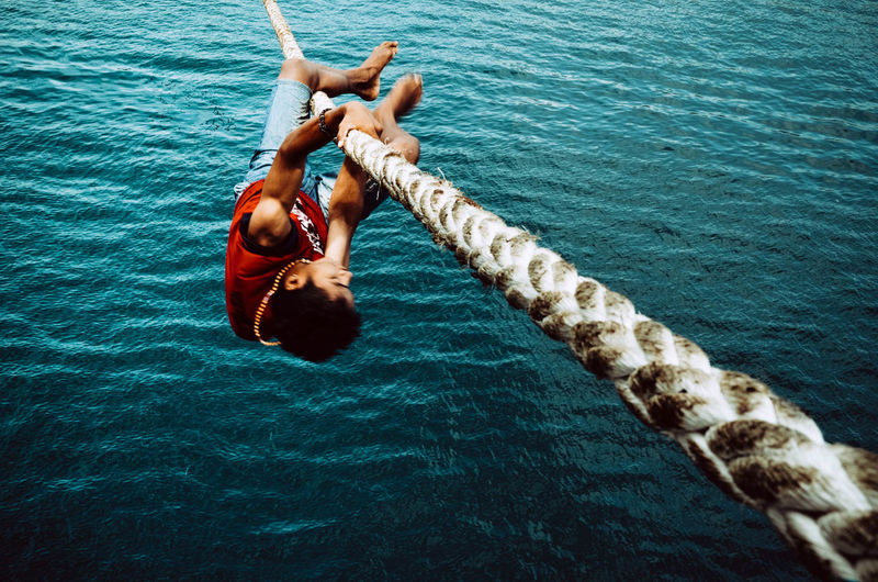 Full length of young man hanging on rope over sea