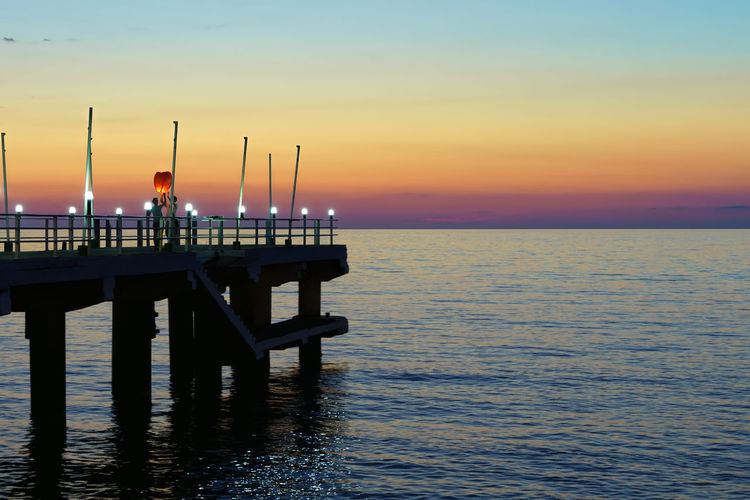 Pier on sea at sunset