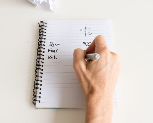 Cropped hand of man writing on book