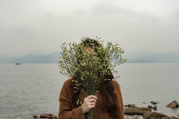 Woman Covering Face With Flowers By Sea Against Sky