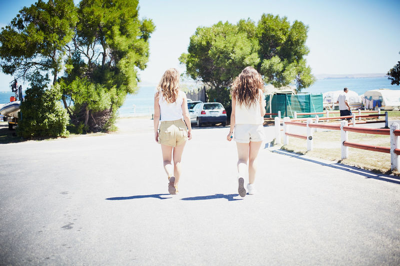 Childhood Day Friendship Full Length Leisure Activity Outdoors Real People Rear View Shadow Sky Sunlight Togetherness Tree Two People Young Adult Young Women