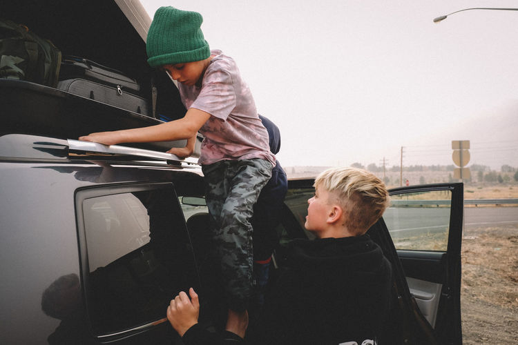 Father and son while sitting on car