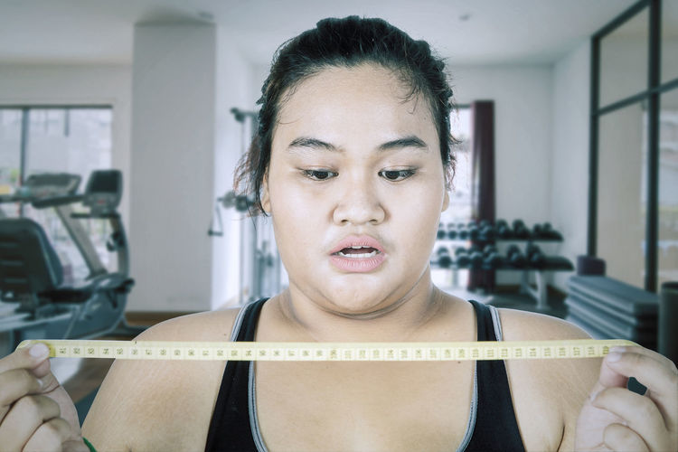 Woman looking at tape measure in gym