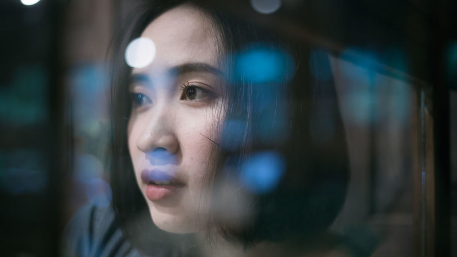 Close-up of woman looking away seen through window