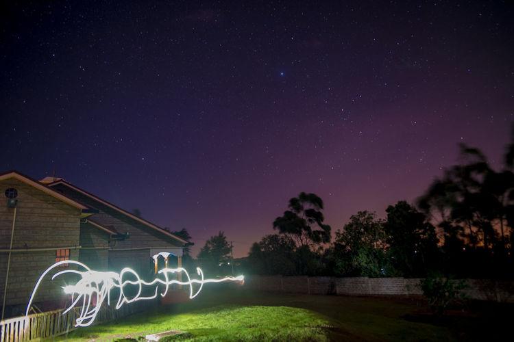 Illuminated light trail against sky at night